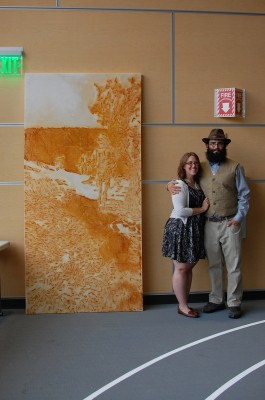 "Jenna Brooks and Bryan Box stand by Box's ""Into the Abyss"" artwork, which he displayed in the Sept. 11 ""Service Before Self"" art auction. The piece is still available for display, he says. (Photo courtesy of Bryan Box)"